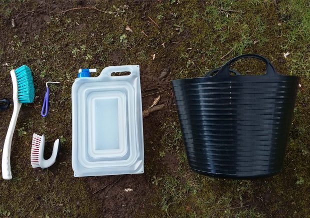 Equipment for a biosecurity kit is in a line on the ground outside. From left to right there is a brush, bootpick, water container and bucket