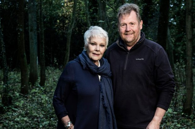 Judi Dench stands to the left of the image looking at the camera and Tony Kirkham stands next to her on the right also looking at the camera. They are central in the image