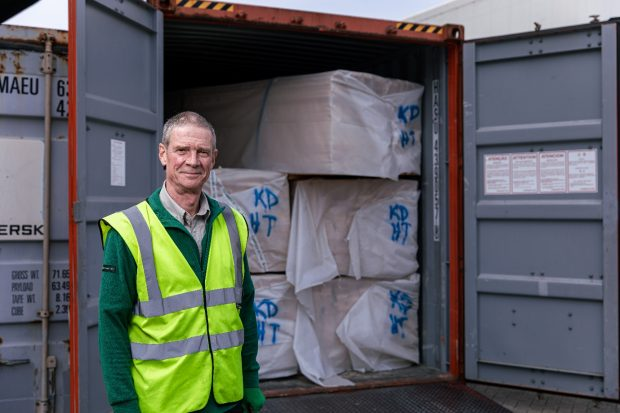 A man in a high vis jacket stands in front of a container full of wood products