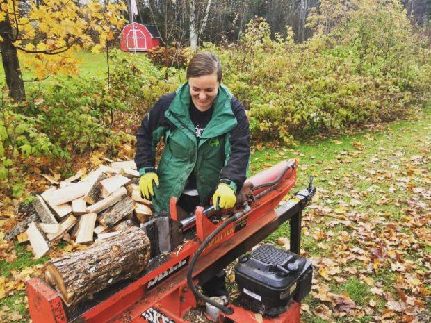 A woman smiling wearing a green coat using a log splitter