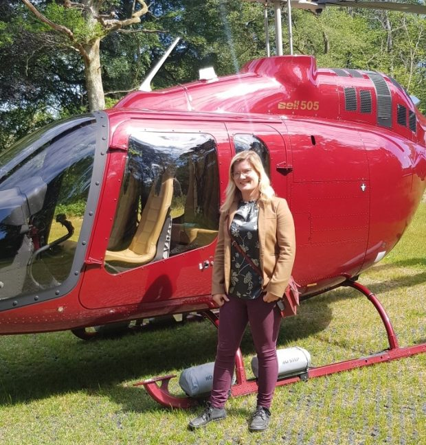 A woman with light brown hair and glasses stands in front of a red helicopter with her hands in her pocket