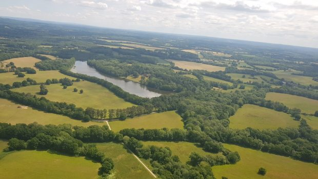 An ariel view of fields, woodland and lakes