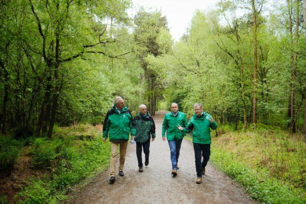 Four men walk through a forest talking